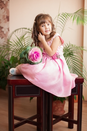Beautiful little girl model view in a luxury pink dress and flower posing at home on the table Stock Photo - 16711031