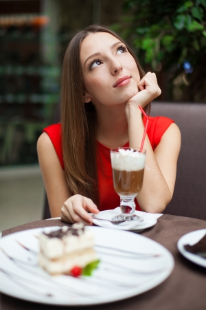 Attractive young woman has a rest in restaurant in front of her on the table tiramisu cake and drink coffee latte in a glass beaker  Stock Photo - 16715505