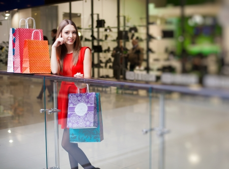 Beautiful young woman in a luxurious red dress posing with shopping bags in mall on the background of shop windows  Series  Stock Photo