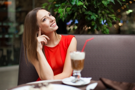 Attractive young woman has a rest in restaurant in front of her on the table tiramisu cake and drink coffee latte in a glass beaker Stock Photo - 16793806