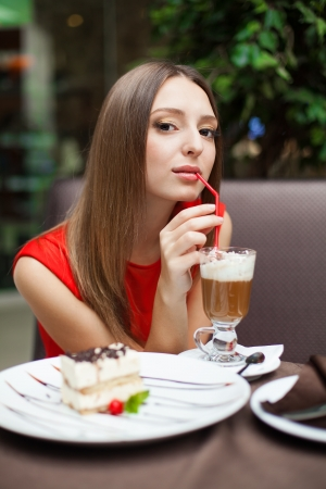 Attractive young woman has a rest in restaurant in front of her on the table tiramisu cake and drink coffee latte in a glass beaker Stock Photo - 16793803