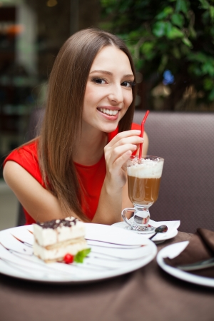 Attractive young woman has a rest in restaurant in front of her on the table tiramisu cake and drink coffee latte in a glass beaker  photo