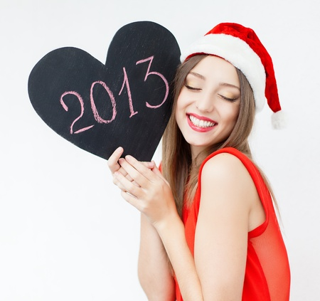 Attractive young woman posing in red cap on white background with sign New Year  2013   Series  photo
