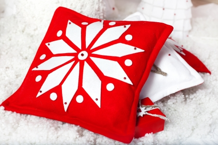 Embroidered snowflake on red and white pillow  Christmas decoration in studio on white background  Series