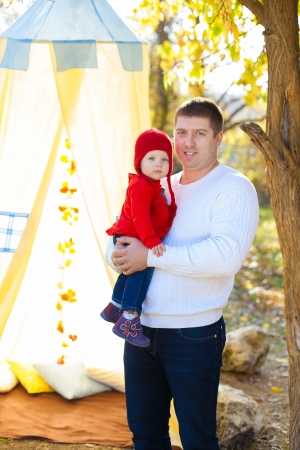 Father hugging his little baby  Young family posing in park on background of the tent and tree  Stock Photo - 16884091