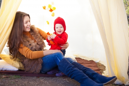 Happy mother and her baby posing sitting in tent outdoor  photo