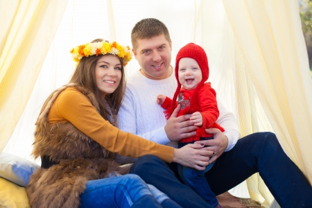 Happy young family with daughter posing sitting in tent in a park Stock Photo - 16884099
