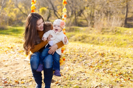happy mother and her little baby swing on the background of trees and sky in the park Stock Photo - 16884079