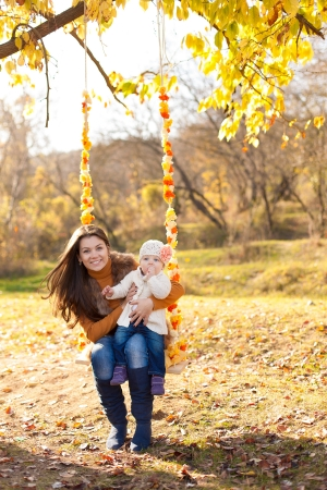 happy mother and her little baby swing on the background of trees and sky in the park  photo
