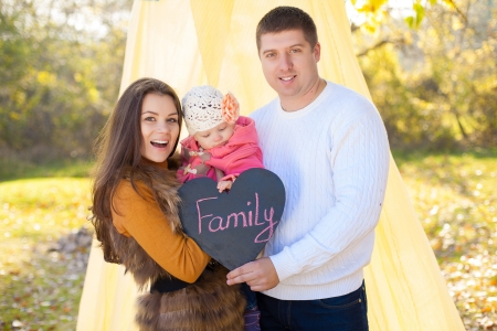 Happy young family mom dad and little baby posing on background of the tent and trees  Held in the hand plate in form of heart with the words FAMILY Stock Photo - 16884103