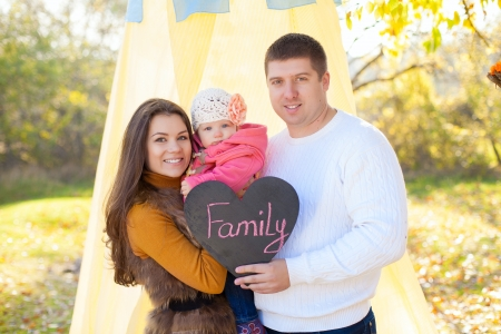 Happy young family mom dad and little baby posing on background of the tent and trees  Held in the hand plate in form of heart with the words FAMILY Stock Photo - 16884087