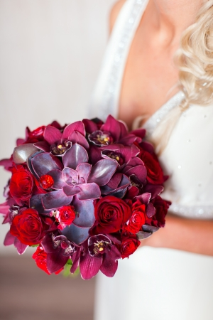 Closeup of bride hands holding beautiful wedding bouquet of red photo