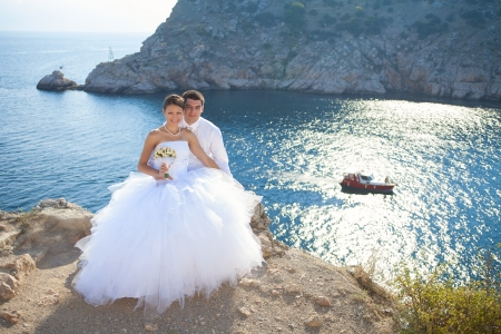 wedding  young bride and groom hugging on cliff background of blue sea in summer  Series photo