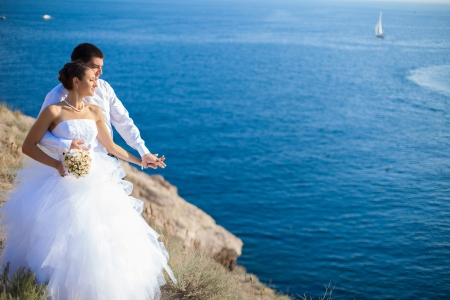 Couple in love young bride and groom dressed in white hugging on cliff background of blue sea in their wedding day in summer