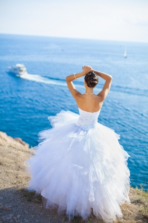 Happy bride in white dress stands on cliff on background blue sea in her wedding day in summer