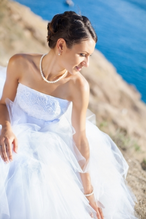 Happy bride in white dress on cliff on background blue sea in her wedding day in summer Stock Photo