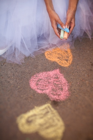 Bride hands drawing hearts with colored chalks on