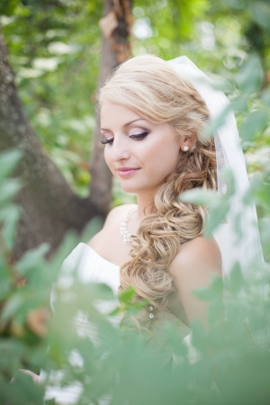 Attractive bride posing in the green leaves of the tree in her wedding day Stock Photo - 17152782