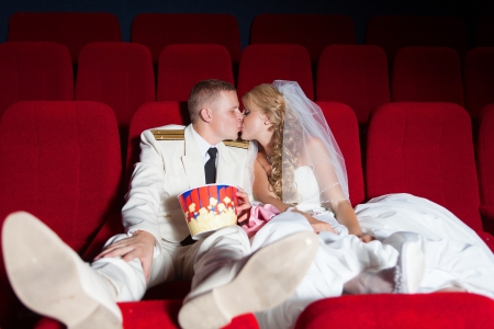 Wedding  kissing bride and groom posing as spectator in the cinema photo
