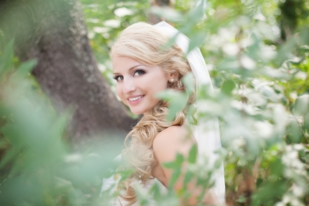 Attractive bride posing in the green leaves of the tree in her wedding day Stock Photo - 17152773