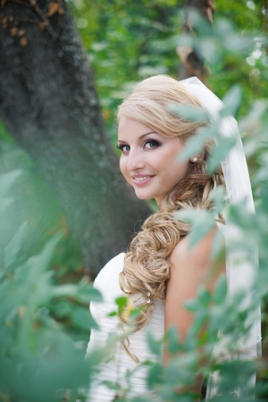 Attractive bride posing in the green leaves of the tree in her wedding day Stock Photo - 17152735