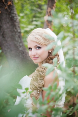 Attractive bride posing in the green leaves of the tree in her wedding day Stock Photo - 17152777
