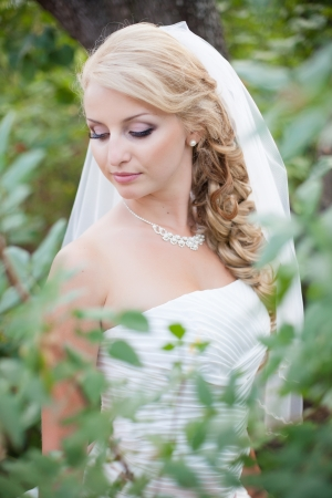 Attractive bride posing in the green leaves of the tree in her wedding day Stock Photo - 17152780