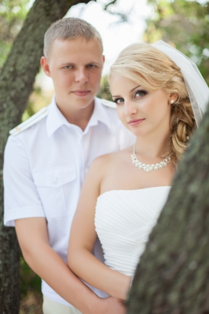 young couple posing near a tree in the forest their wedding day in the summer Stock Photo - 17152791