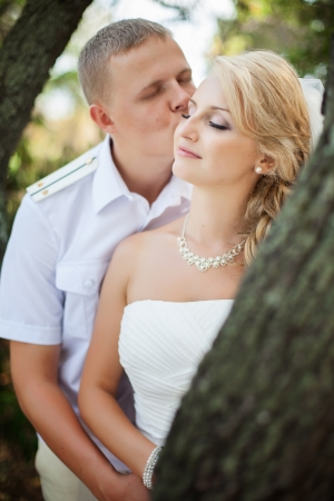 young couple posing near a tree in the forest their wedding day in the summer photo