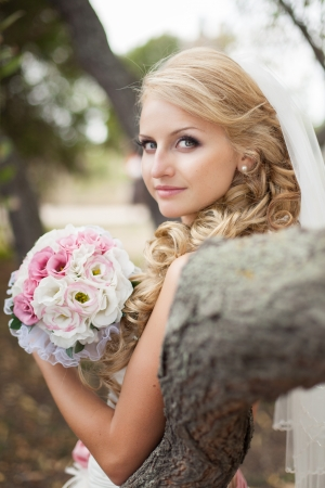 Attractive bride posing in the green leaves of the tree in her wedding day photo
