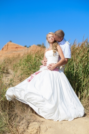 bride and groom embracing on the beach standing in the reeds Stock Photo - 17152734