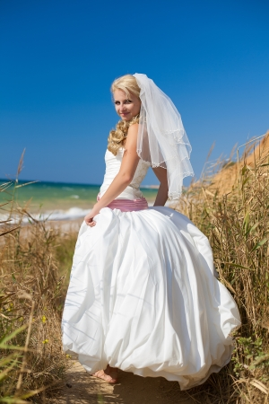 bride on beach standing in the reeds, posing in her wedding day in summer Stock Photo - 17152778
