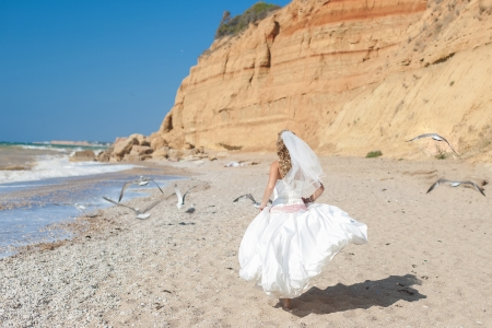 Attractive bride posing on the beach smiling and running on sand Stock Photo - 17152733