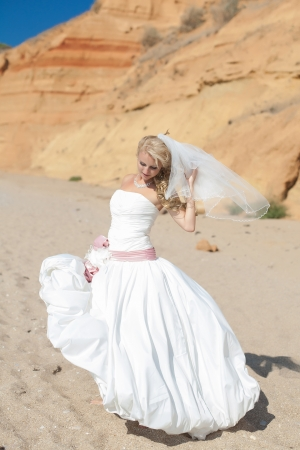 Attractive bride posing on the beach smiling and running on sand Stock Photo - 17152805