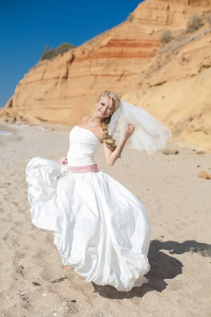 Attractive bride posing on the beach smiling and running on sand photo