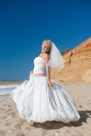 Attractive bride posing on the beach smiling and running on sand Stock Photo - 17152800