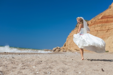 Attractive bride posing on the beach smiling and running on sand Stock Photo - 17152794