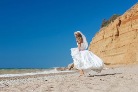 Attractive bride posing on the beach smiling and running on sand Stock Photo - 17152796