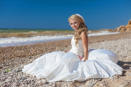 Attractive smiling bride sitting on the sand by the sea photo