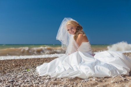 Attractive smiling bride sitting on the sand by the sea Stock Photo - 17152767