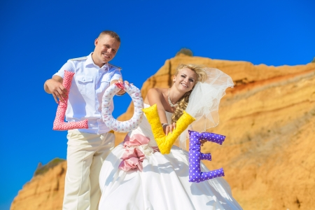 wedding  couple posing on the shore and holding the letters with the word  LOVE Stock Photo - 17152789