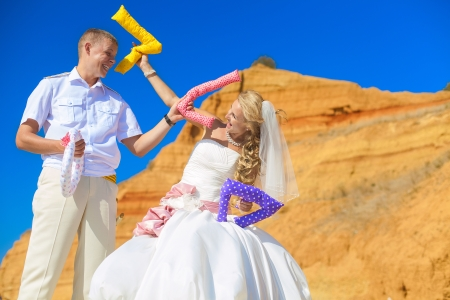 Wedding  couple posing on the shore and jokingly fight letters of the word  LOVE Stock Photo - 17152795