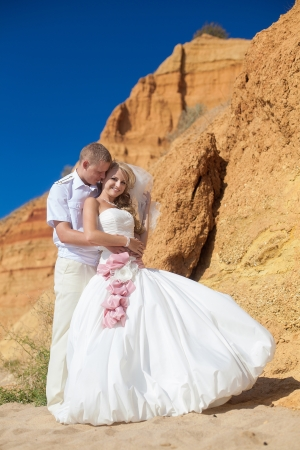 Couple in love bride and groom pose for embracing on background the rocks standing on sand by the sea, enjoying the moments of happiness in their wedding day  photo