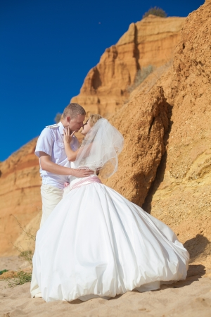 Couple in love bride and groom pose for embracing on background the rocks standing on sand by the sea, enjoying the moments of happiness in their wedding day  Stock Photo - 17152768