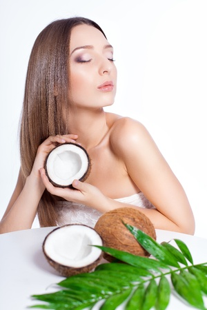 beautiful woman with perfect skin holding coconut over white background Stock Photo - 17229234