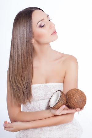 beautiful woman with perfect skin holding coconut over white background Stock Photo - 17229224