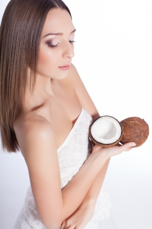 beautiful woman with perfect skin holding coconut over white background Stock Photo - 17229230