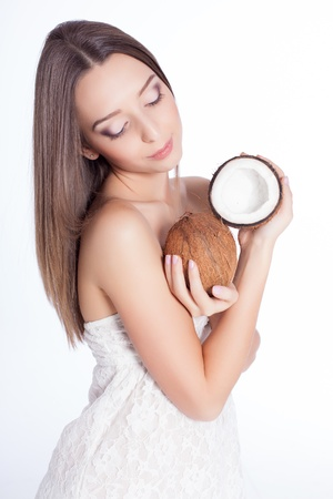 beautiful woman with perfect skin holding coconut over white background Stock Photo - 17229228