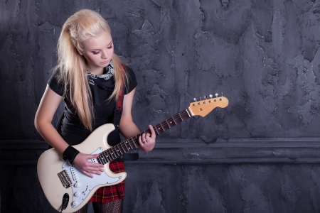 gitar: teenager rockstar with electric guitar against wall background LANG_EVOIMAGES