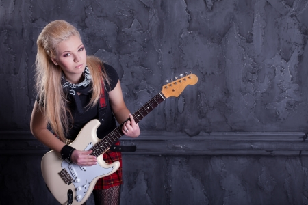 teenager rockstar with electric guitar against wall background Stock Photo - 17229236